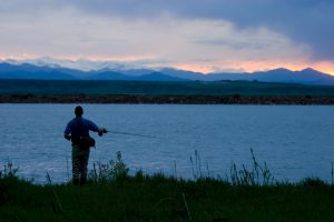 Fly fisherman on a beautiful Colorado summer evening with the Rockies and Mount Evans in the background.